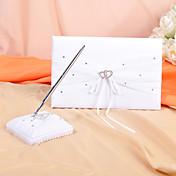 ラインストーンのアクセントと白のサテンで設定された結婚式のゲストブックとペン